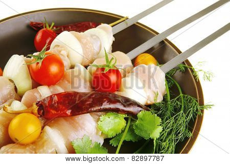 raw chicken kebabs served on dark plate with vegetables