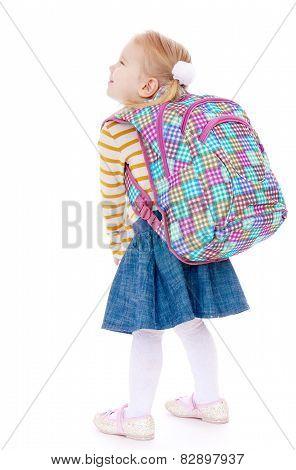 pretty girl schoolgirl with satchel on his shoulders.