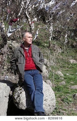 Hombre descansa sobre una piedra