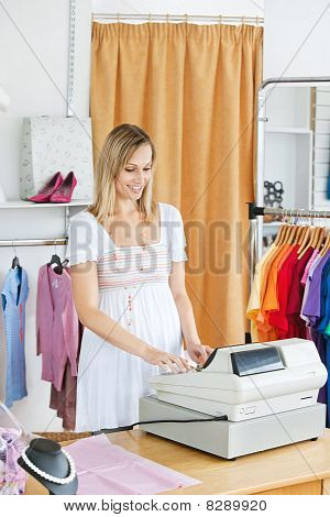 Elegant Saleswoman Standing At The Cash Register