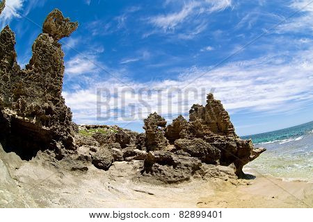 Big rock on the beach with blue clouds as background