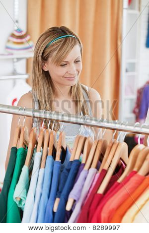 Captivating Young Woman Choosing A Colorful Shirt