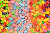 foto of gumballs  - closeup of assorted candy in a row making a background - JPG