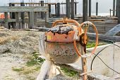 picture of mixer  - Dirty concrete mixer on a building site - JPG