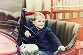 stock photo of steers  - A happy young boy sits in an old shiny vintage red fire truck holding on to the steering wheel looking out - JPG