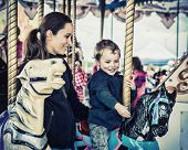 picture of amusement park rides  - A happy mother and son are riding on a carousel together smiling and having fun at an amusement park - JPG