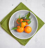 pic of clementine-orange  - Clementine tangerines with green leaves on white wooden background in a grey bowl - JPG