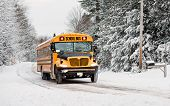 stock photo of tree lined street  - A school bus drives down a snow covered rural country road lined with snow covered trees after a snow storm during the winter season - JPG