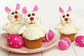 stock photo of easter eggs bunny  - Cute spring bunny cupcakes on pink plate with Easter eggs - JPG