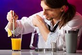foto of bartender  - Young stylish man bartender preparing serving alcohol cocktail drink over bar counter - JPG