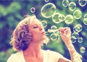 image of blowing  - a beautiful woman blowing bubbles toned with a retro vintage instagram filter effect app or action  - JPG