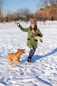 stock photo of pit-bull  - Young woman playing with dog breed American Pit Bull Terrier in winter  - JPG
