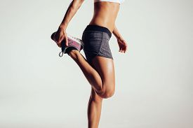 picture of calf  - Cropped image of a fitness woman stretching her legs against grey background - JPG