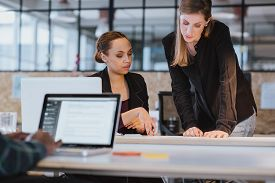 picture of coworkers  - Shot of two coworkers going through paperwork together - JPG