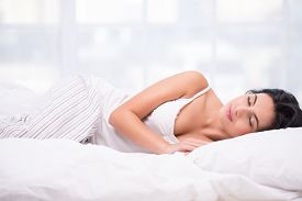 picture of pyjama  - Beautiful young dark haired woman sleeping on a white bed wearing striped pyjamas - JPG