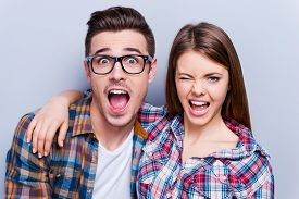 picture of couple  - Beautiful young loving couple making faces at camera while standing against grey background - JPG