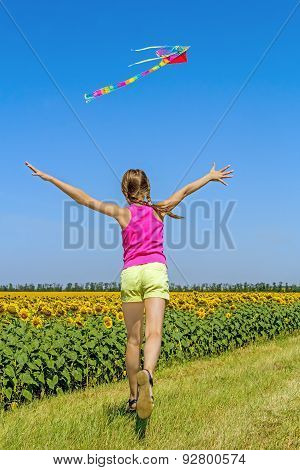 Girl Running After The Kite Along The Field