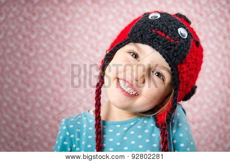 Portrait Of Little Girl Smiling And Being Happy. Child Is Wearing A Woolen Cap In The Shape Of Ladyb