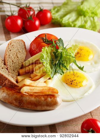 Fried eggs with sausage and fries