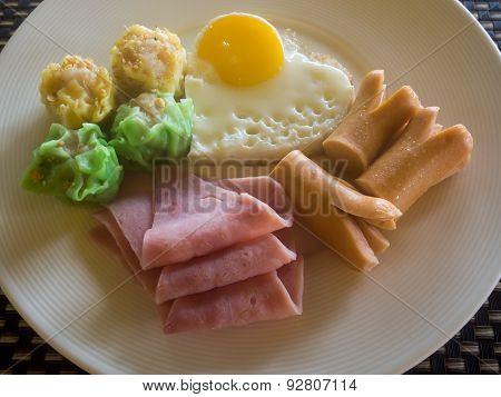 Breakfast of eggs bacon hotdogs dumplings.