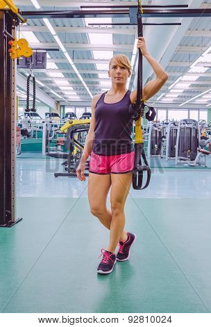 Woman standing out with a fitness straps
