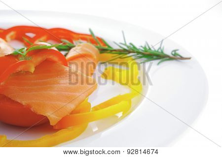 smoked salmon slices with vegetabls over white plate