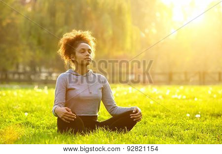 African American Woman Meditating In Nature