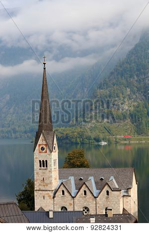 Slender belfry church on the shore of Lake Hallstatt. On the opposite shore of the lake - the beautiful mountains overgrown with forests. The most picturesque small town in Austria - Hallstatt