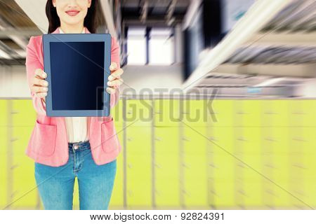 Elegant brunette using tablet against locker room
