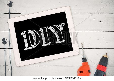 The word diy against tools and tablet on wooden background