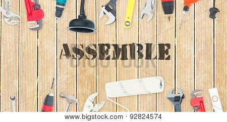 The word assemble against diy tools on wooden background