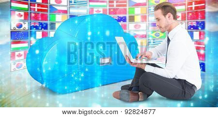 Smiling businessman sitting on floor using laptop against digitally generated black and blue matrix