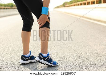 woman runner hold her injured leg