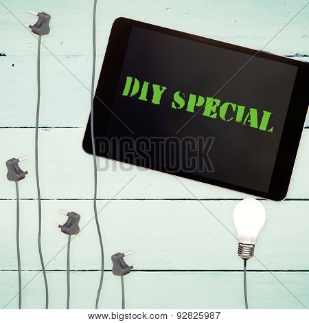 The word diy special against bulbs and tablet on wooden background