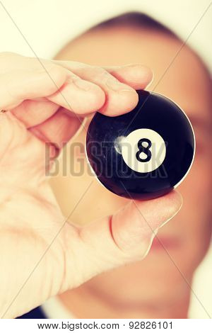 Businessman holding billiard eight ball in his hand.