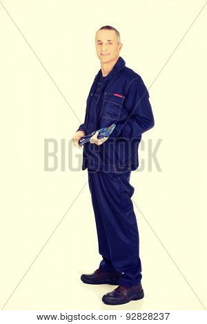 Smiling mature plumber holding a wrench.