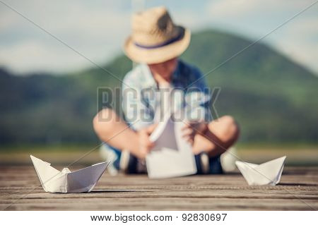 Boy Make A Paper Boat Sitting On The Wooden Pier