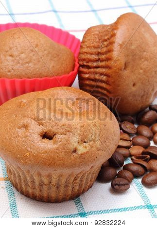 Fresh Baked Muffins And Coffee Grains On Colorful Cloth