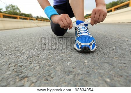 young woman runner tying shoelaces on city birdge road