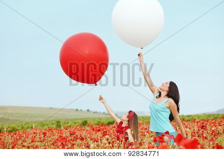 Mother and her 7 years old preteen child playing with big balloons in spring flower field