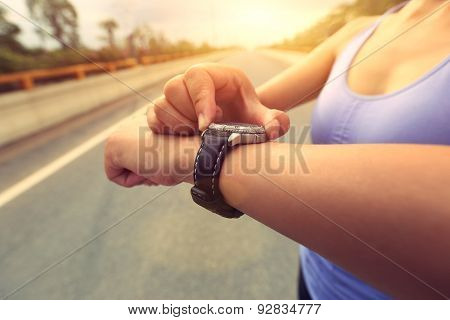 young woman jogger ready to run set and looking at sports smart watch, checking performance or heart