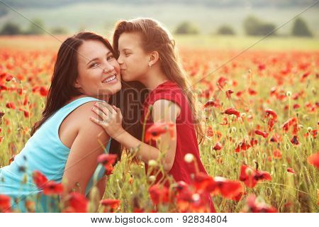 Mother and her 7 years old preteen child playing in spring poppy field in soft sunlight. Daughter kissing mom.