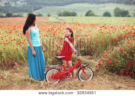 Preteen girl on bicycle with mother in spring field