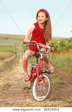 Preteen girl on bicycle in spring field