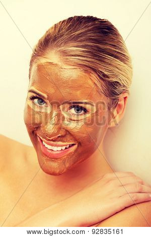 Portrait of happy woman with chocolate mask on face.