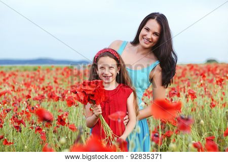 Mother and her 7 years old preteen child playing in spring flower field