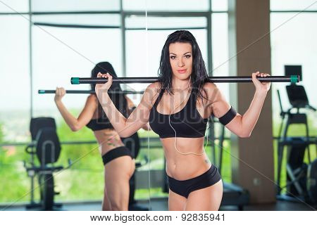 fitness, sport, training, people and lifestyle concept - happy woman flexing muscles with barbell in