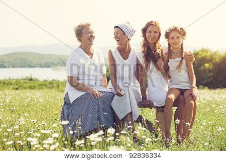 Four generations of beautiful women sitting together in a camomile field and smiling