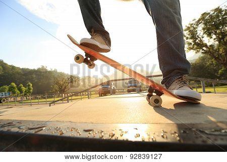 skateboarder legs riding on skateboard at skatepark ramp