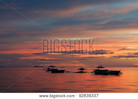 Silhouettes of boats in colourful dramatic sky background in Philippines